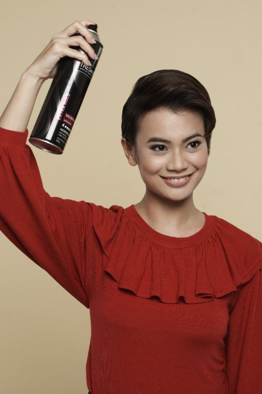 How to style wet to dry pixie: Asian woman spritzing hairspray on her short black hair