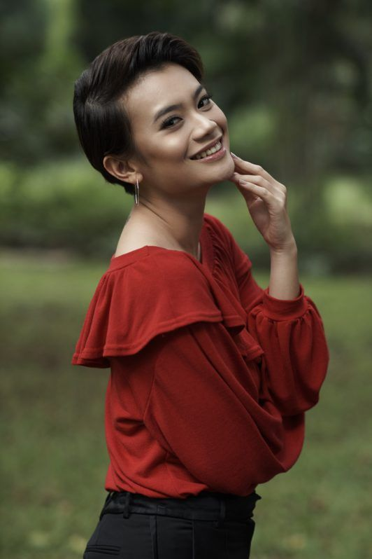 How to style wet to dry pixie cut: Side view shot of an Asian woman with short black pixie cut wearing a red blouse in a park
