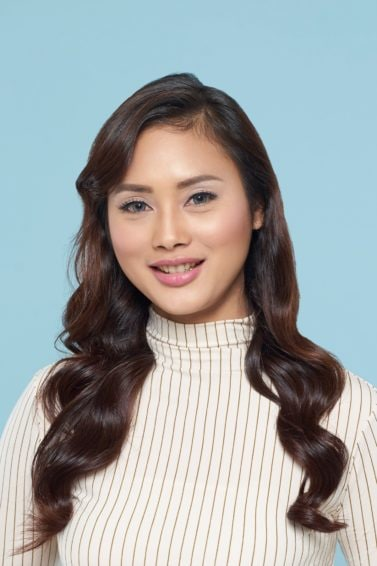 Asian woman with long hair with curly side fringe wearing a white turtleneck top