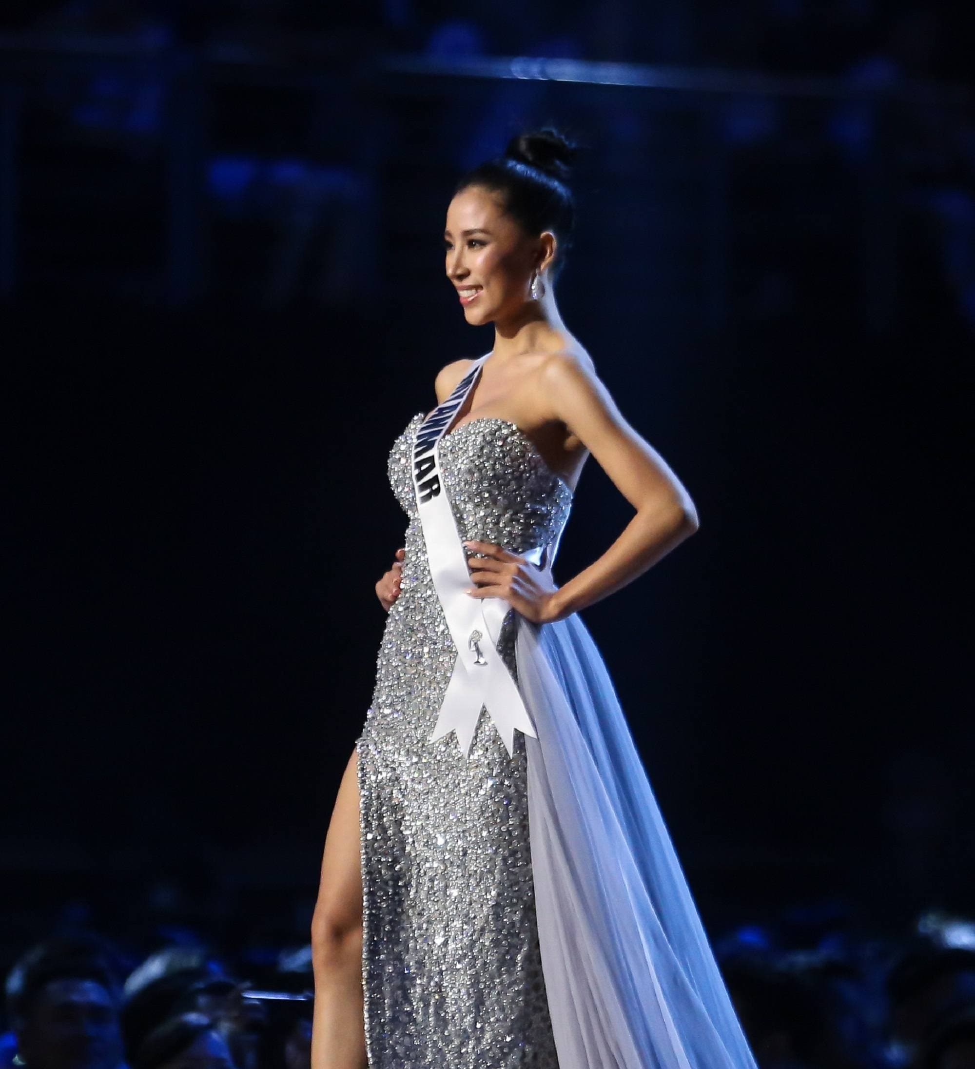 Miss Universe 2018 hairstyles: Miss Myanmar Hnin Thway Yu Aung with black hair in ballerina bun wearing a silver gown on stage