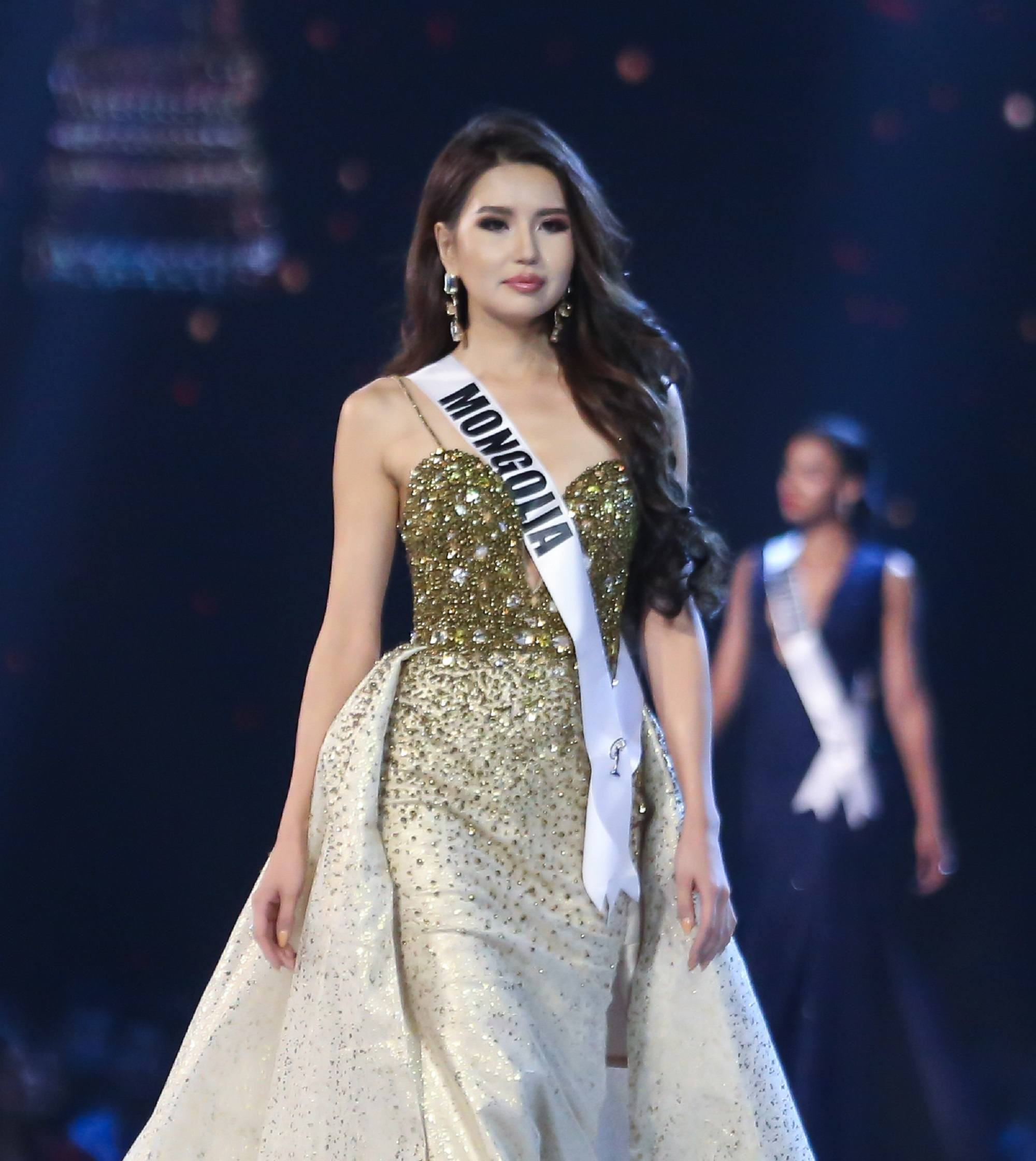 Miss Universe 2018 hairstyles: Miss Mongolia Dolgion Delgerjav with long black wavy hair wearing a green and white evening gown on stage