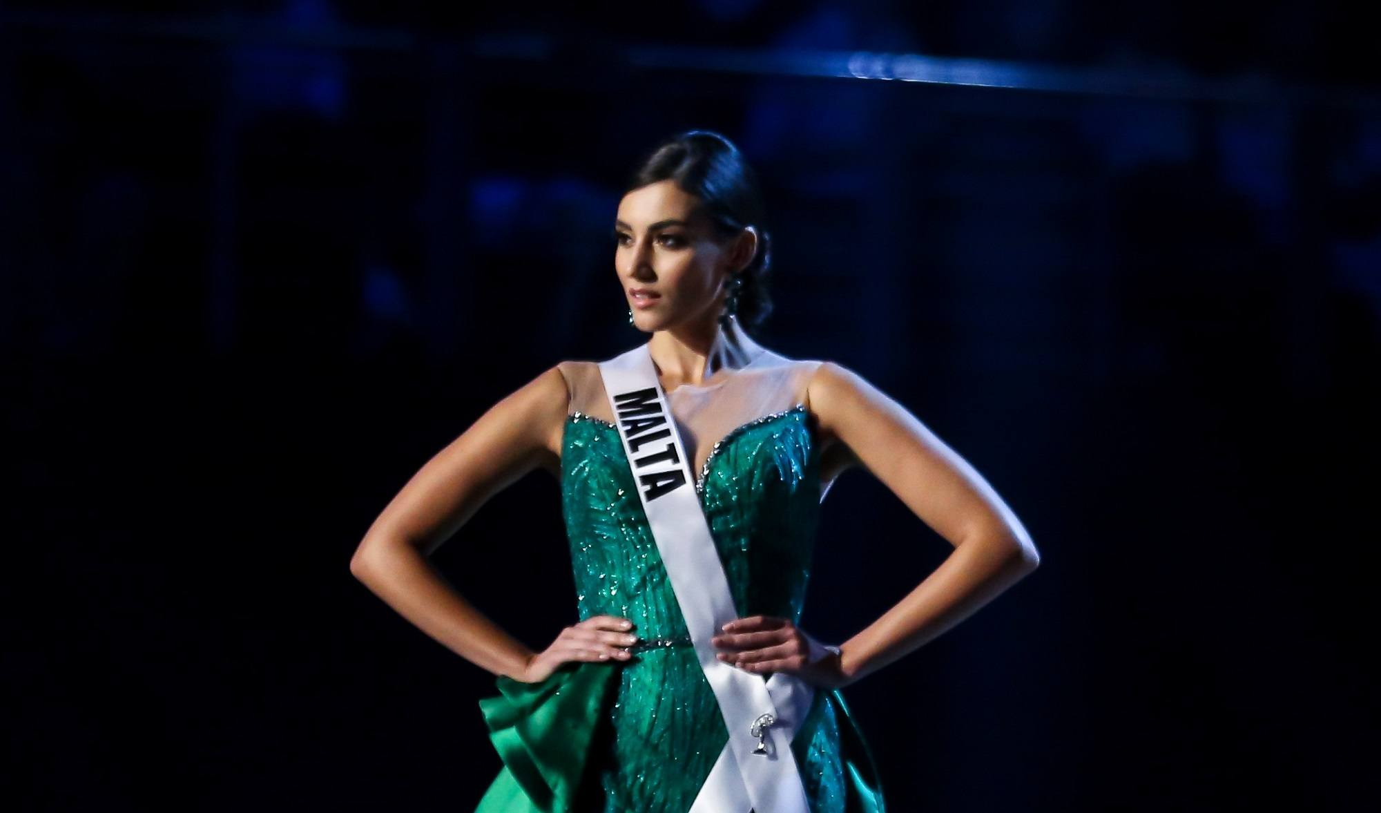 Miss Universe 2018 hairstyles: Miss Malta Francesca Mifsud with black hair in chignon wearing a green evening gown on stage