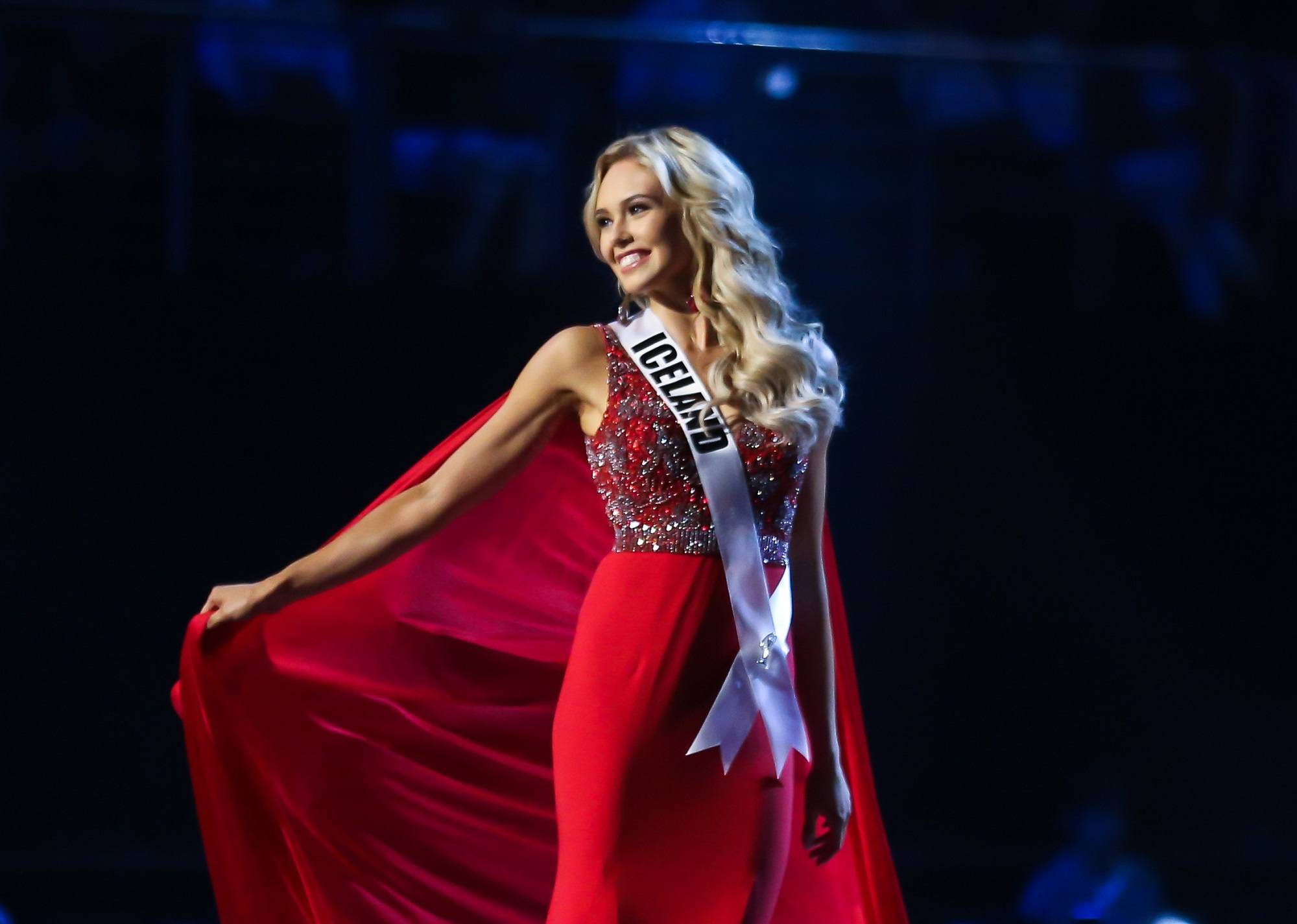 Miss Universe 2018 hairstyles: Miss Iceland Katrin Lea Elenudottir with long blonde wavy hair wearing a red gown on stage