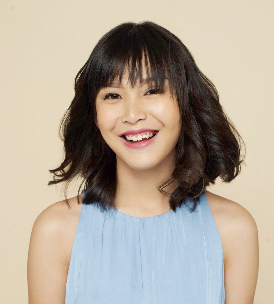 New Year's Eve hairstyles: Closeup shot of an Asian woman with curly long bob wearing a blue sleeveless dress