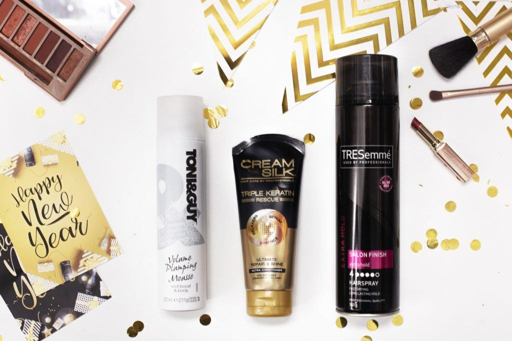 New Year's Eve hairstyles: Flat lay of different hairpsray, hair mousse, conditioner and props