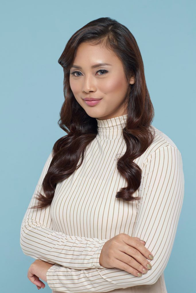 New Year's Eve hairstyles: Asian woman with long dark wavy hair wearing white turtleneck top