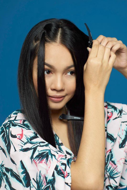 Pipe braids: Closeup shot of an Asian woman styling her long black hair against a blue background