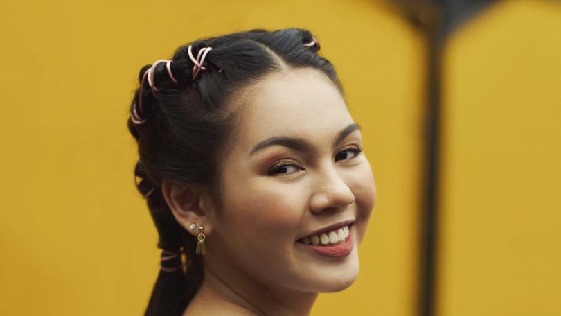 Pipe braids: Closeup shot of an Asian woman with long black hair in pipe braids against a yellow wall
