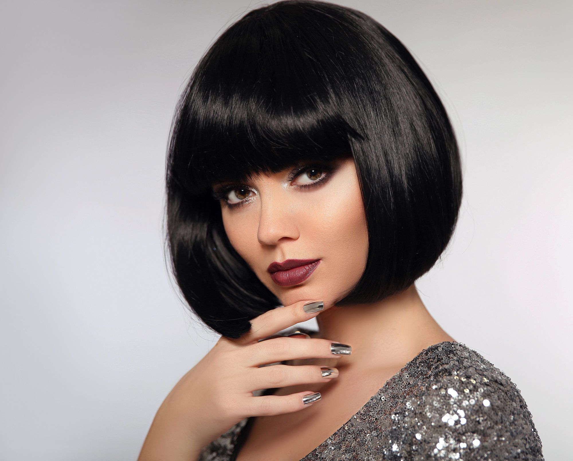 Should I get bangs: Closeup shot of a woman with black bob and blunt bangs wearing a sparkly dress