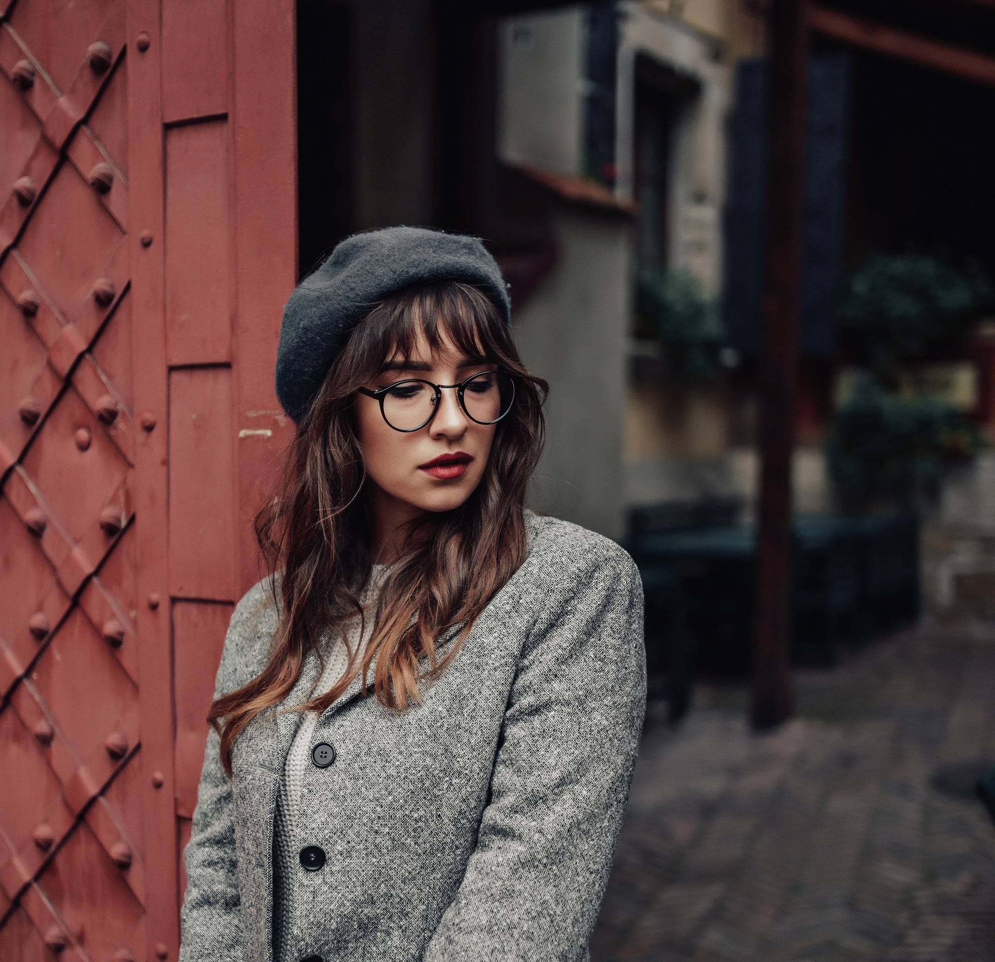 Should I get bangs: Woman with long wavy hair and wispy bangs with eyeglasses wearing a coat and bonnet beside a red gate