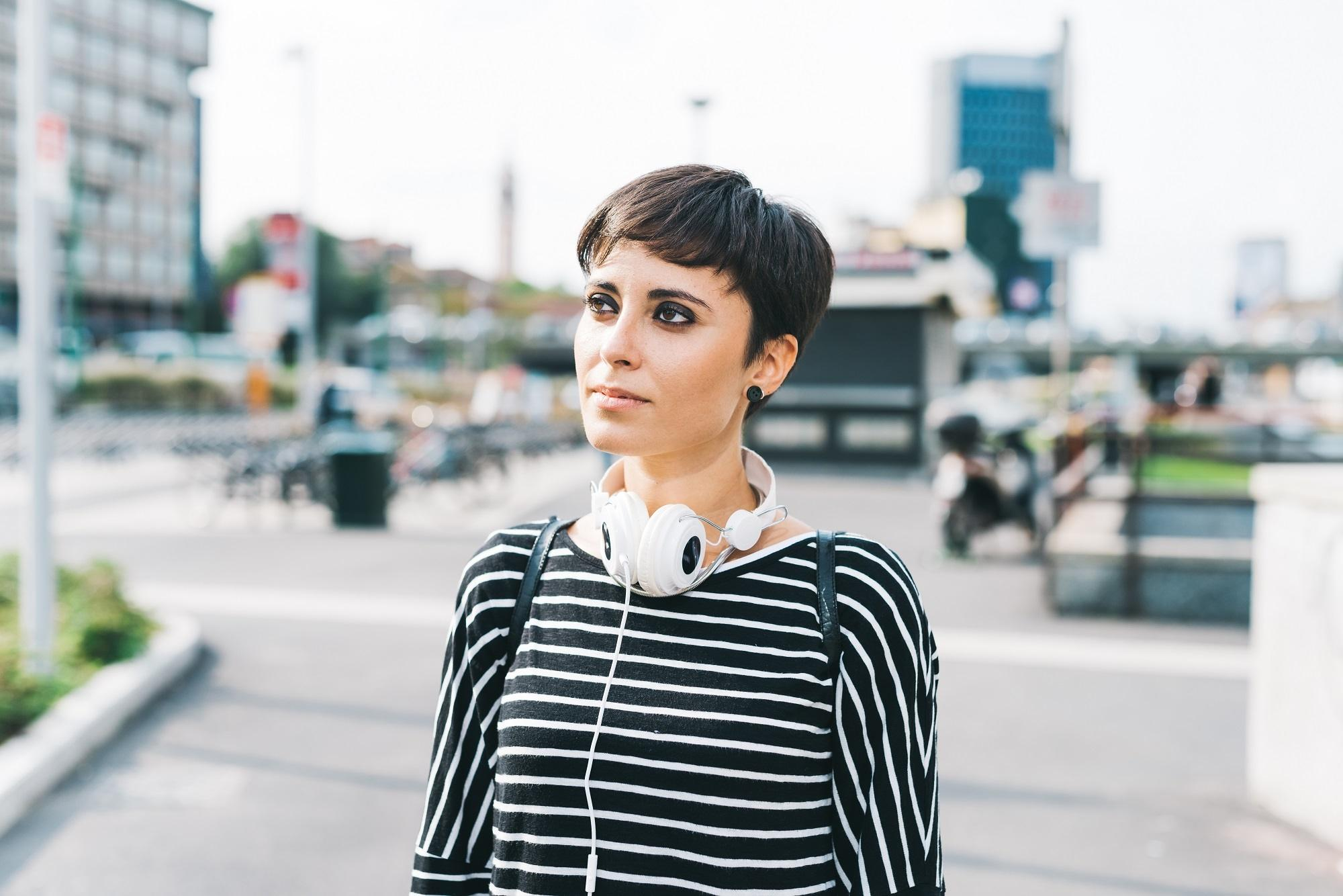 Should I get bangs: Woman with black pixie cut wearing a long-sleeved striped shirt outdoors