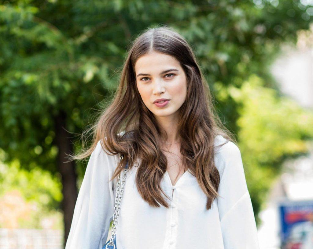 Dark brown hair color: Closeup shot of a woman with long ash brown hair wearing a white blouse outdoors