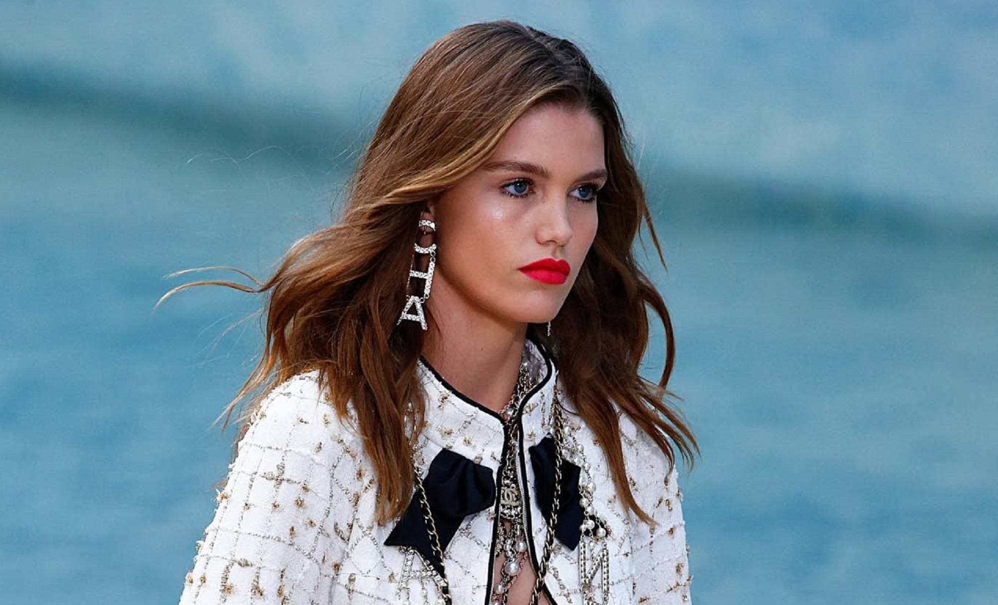 Dark brown hair color: Closeup shot of a woman with long chestnut brown hair wearing a white printed jacket walking in a fashion show