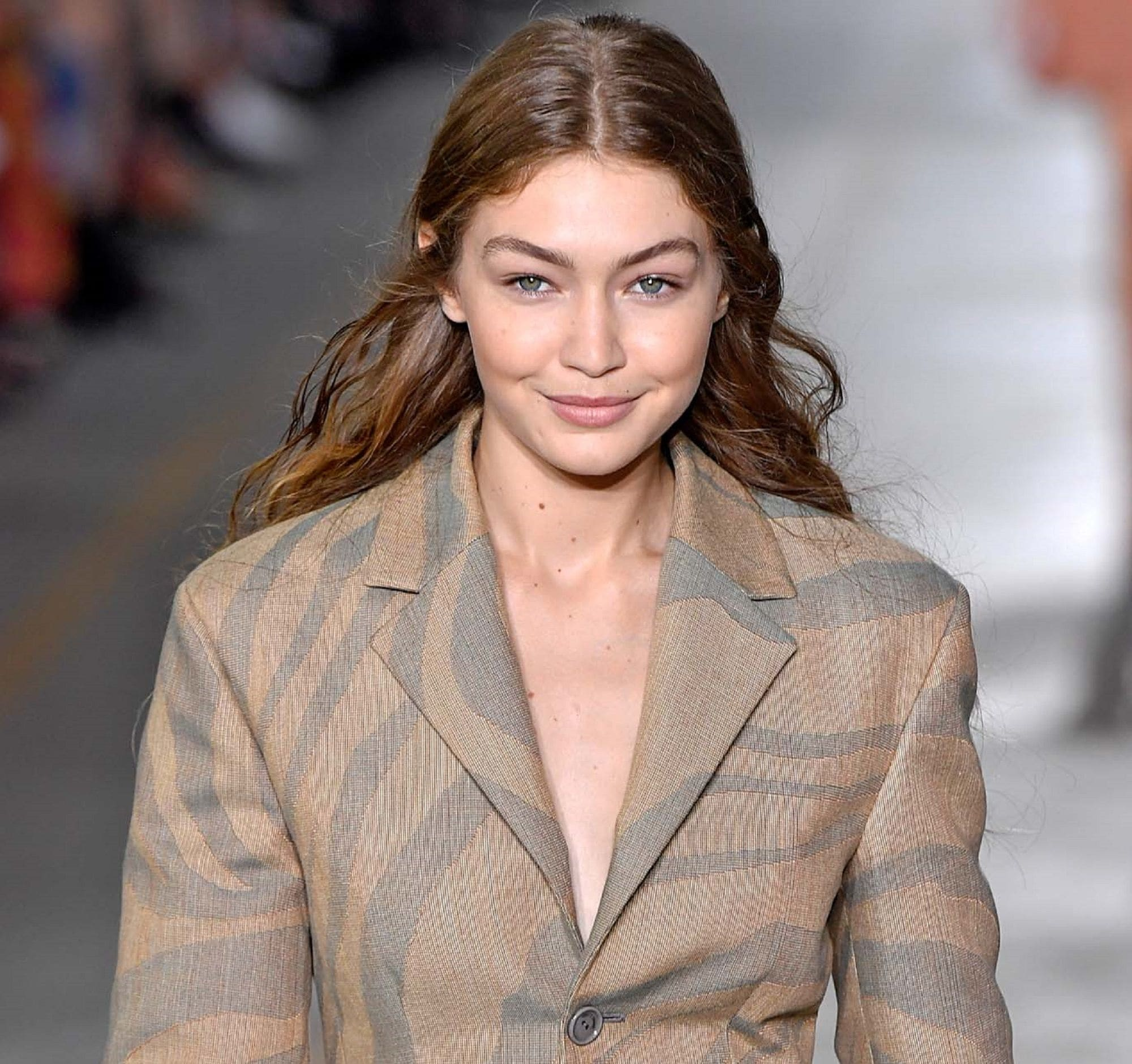 Dark brown hair color: Closeup shot of a woman with long brown hair wearing a light brown coat walking in a fashion show
