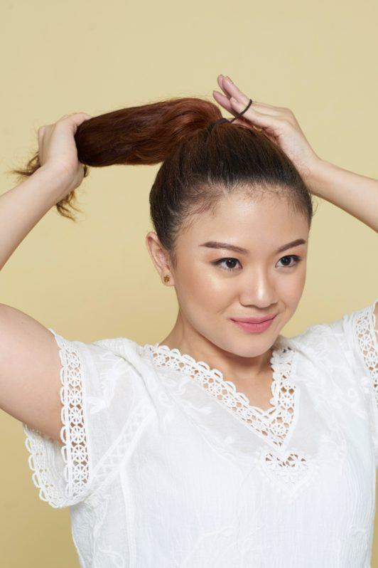 How to style curly hair: Closeup shot of an Asian woman tying her long brown curly hair into a ponytail