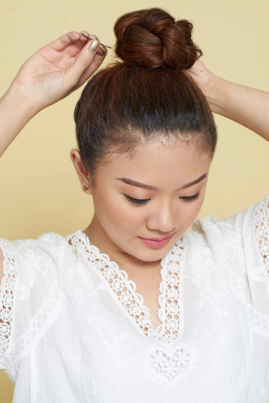 How to style curly hair: Closeup shot of an Asian woman putting her long brown curly hair into a top bun