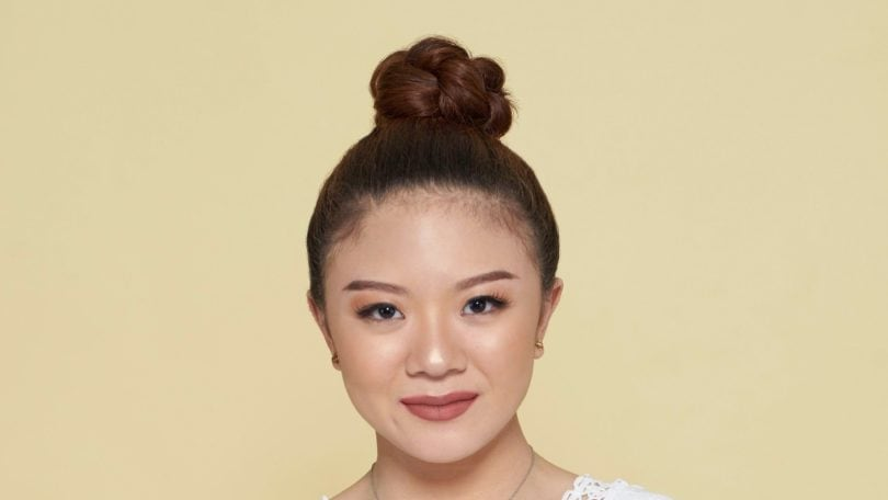 How to style curly hair: Asian woman with brown curly hair in a top bun wearing a white blouse