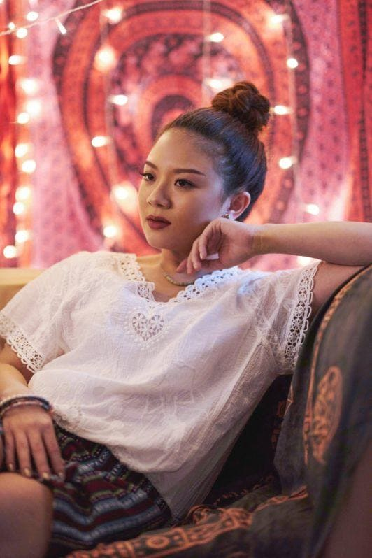 How to style curly hair: Asian woman with brown hair in a top bun wearing a white shirt sitting on sofa with lights in the background