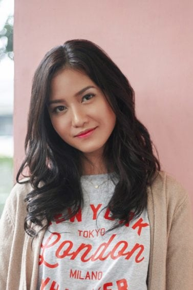 Long wavy hair: Asian woman with long black wavy hair wearing a shirt and cardigan against a pink wall outdoors