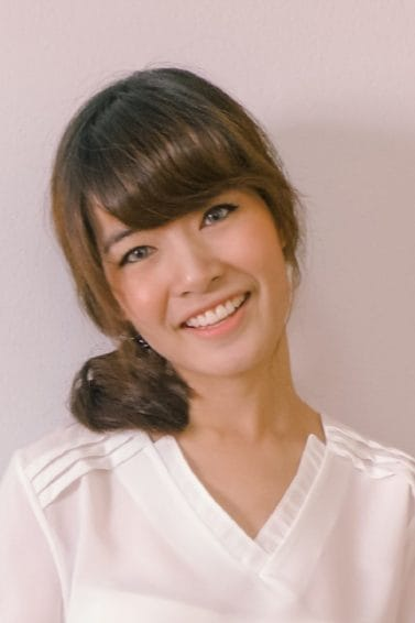 Medium length haircuts with bangs: Closeup shot of a woman with dark brown medium hair with bangs in a side ponytail wearing a white blouse