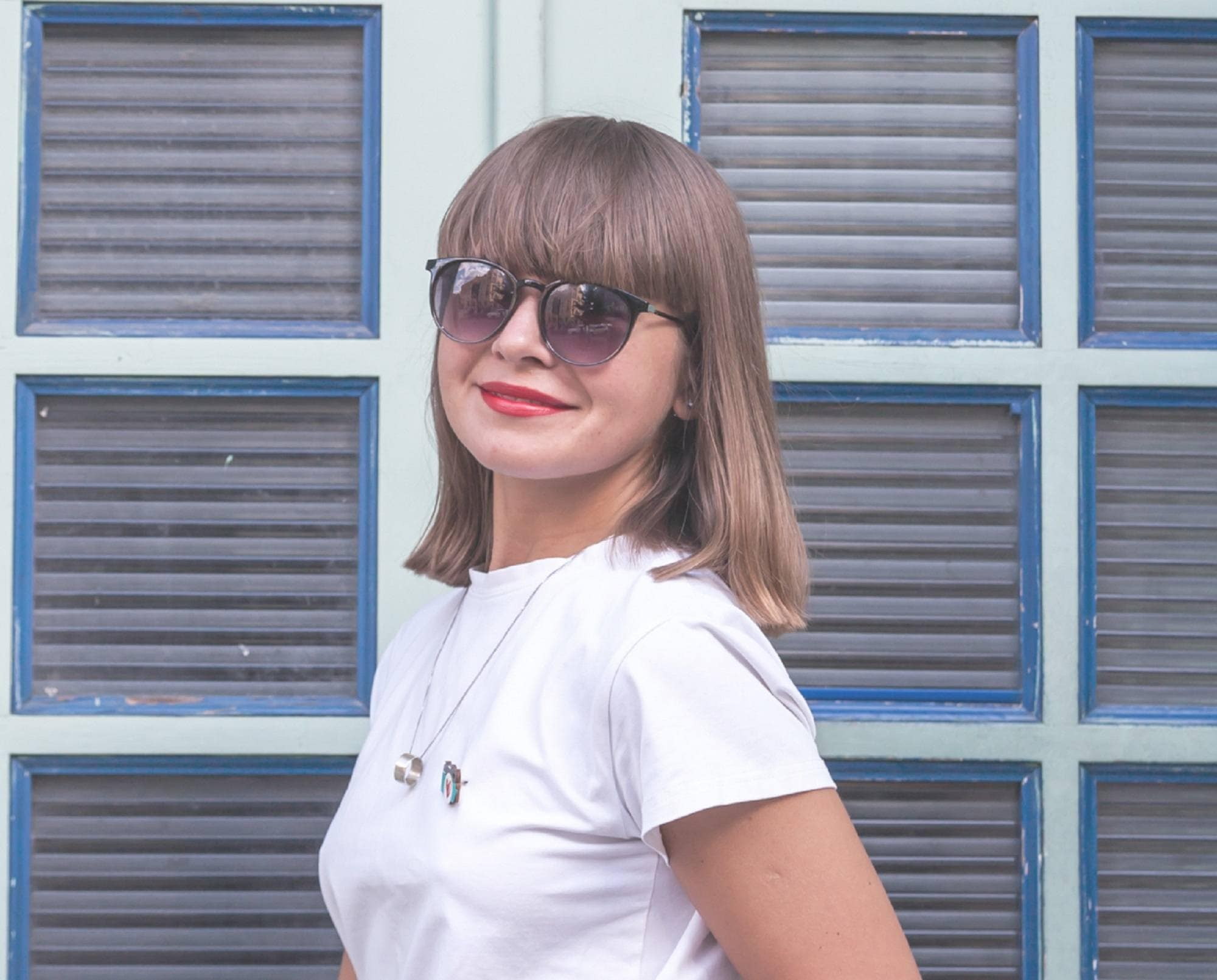 Medium length haircuts with bangs: Closeup shot of a woman with straight brown medium hair with bangs wearing a white shirt against a door