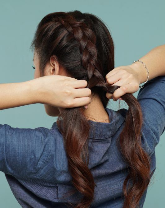 Messy two braids hairstyle: Back shot of Asian woman braiding her long dark hair