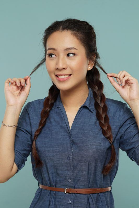 Messy two braids hairstyle: Asian woman with long hair in Dutch braid loosening strands of hair
