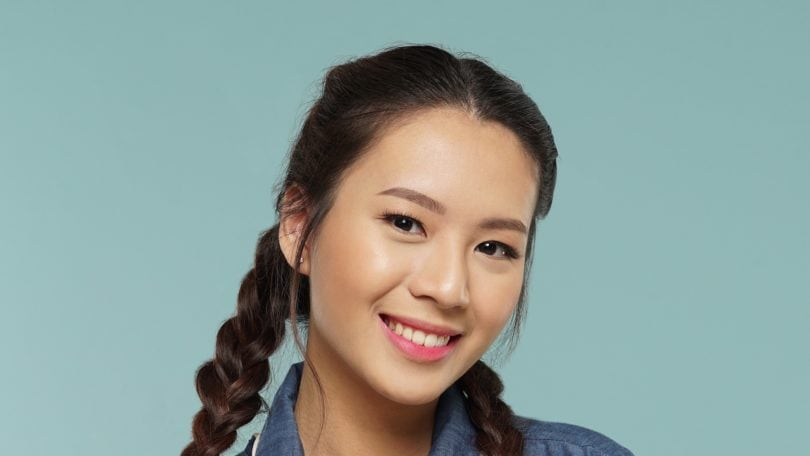 Messy two braids hairstyle: Closeup shot of an Asian woman with long dark hair in messy two braids hairstyle