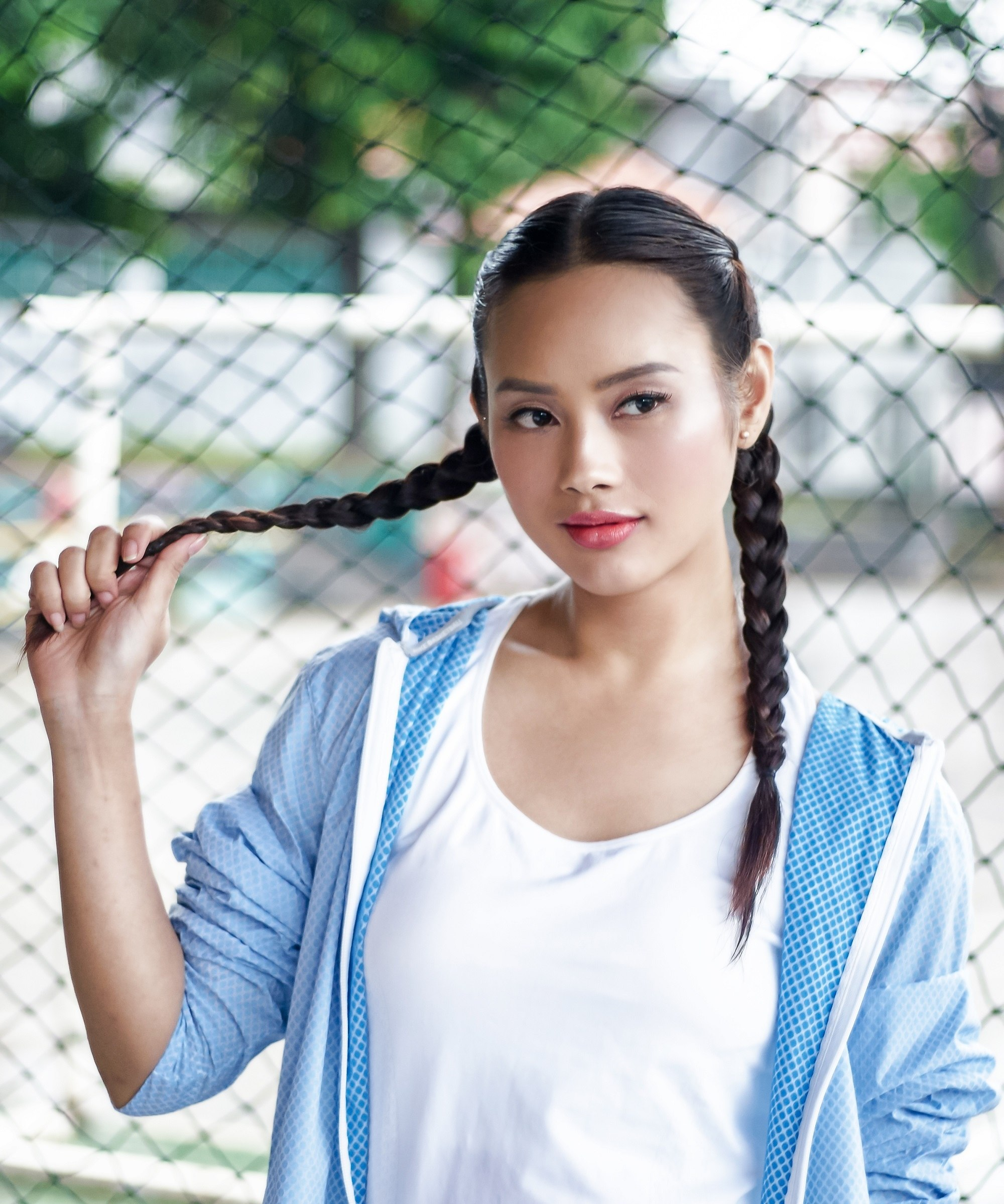 Simple braids: Asian woman wearing a blue jacket with long black hair in boxer braid standing against a fence