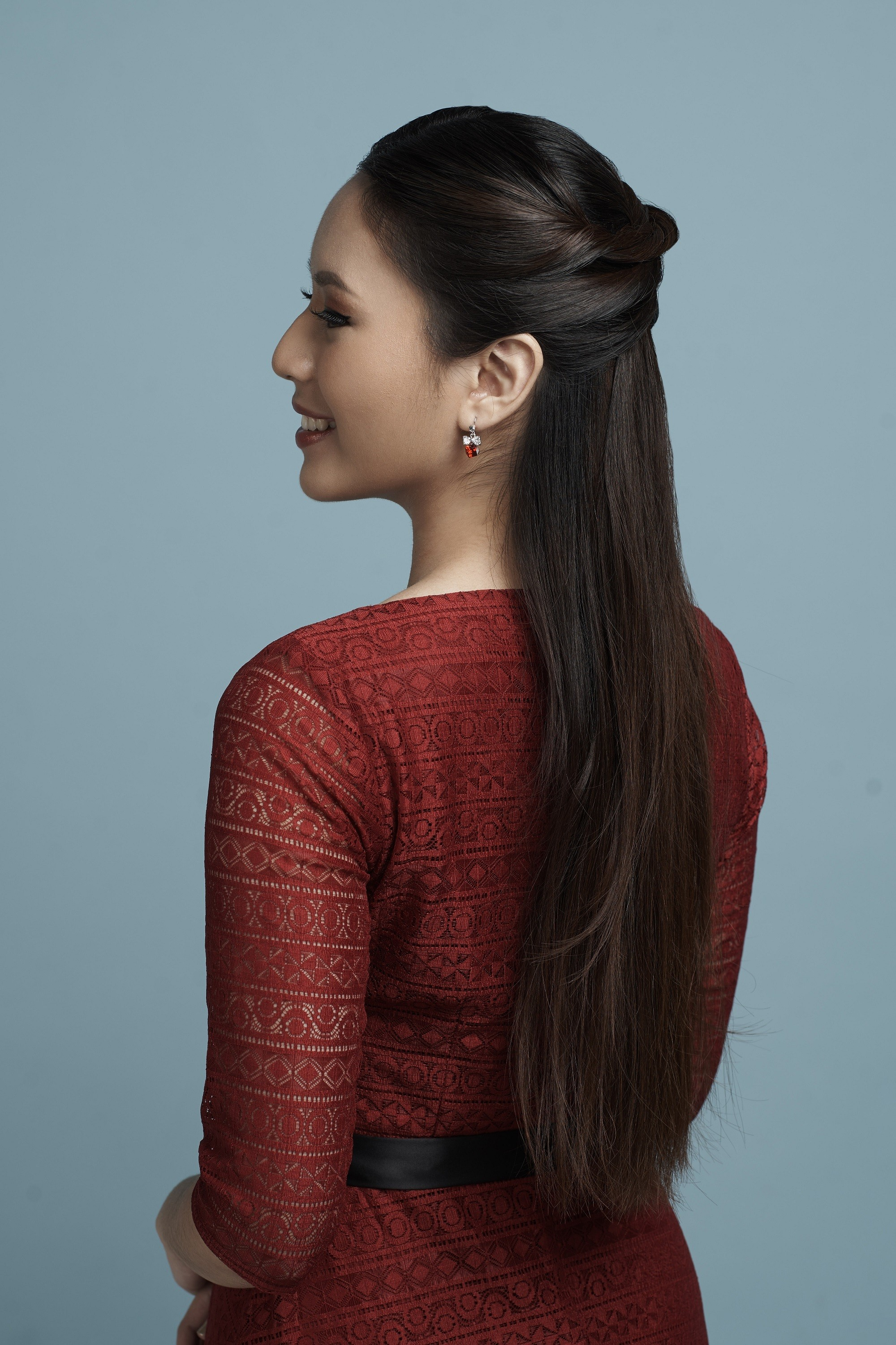 Valentine hairstyles: Back shot of an Asian woman with long black hair in half up hairstyle and wearing a red dress