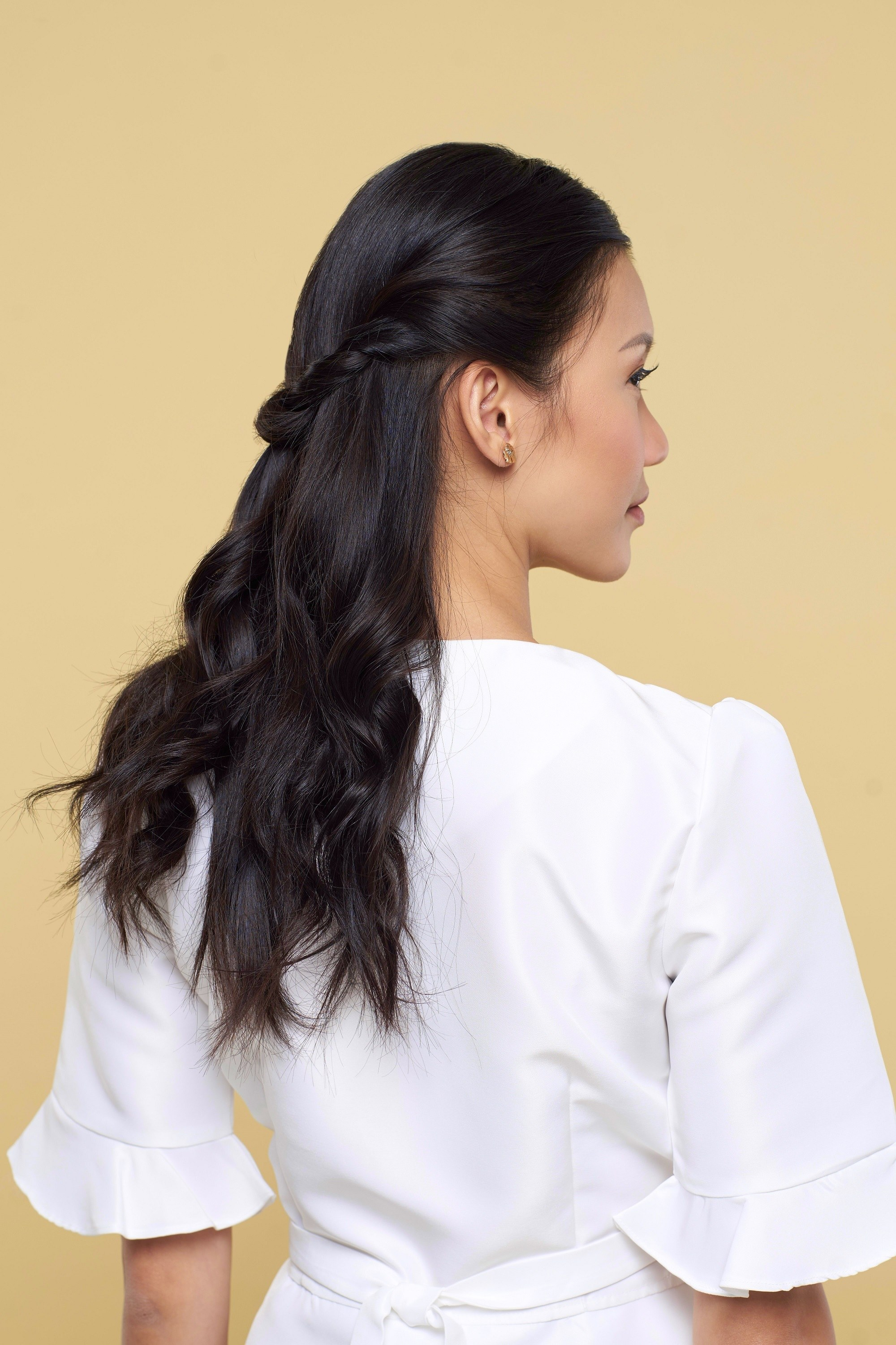 Valentine hairstyles: Back shot of an Asian woman with long black hair in half updo wearing a white blouse