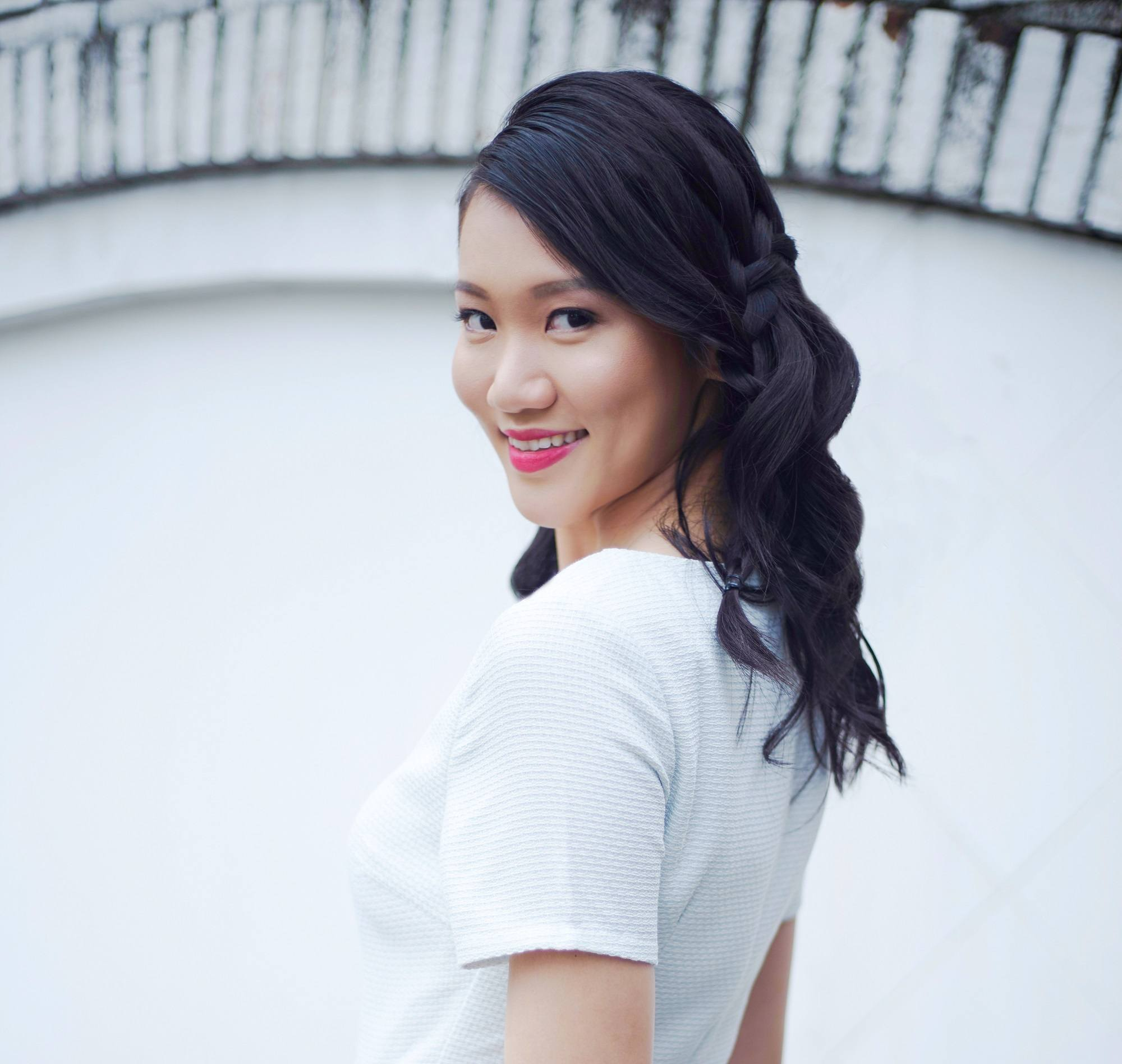 Valentine hairstyles: Closeup shot of an Asian woman with long black hair in waterfall braid wearing a white dress outdoors