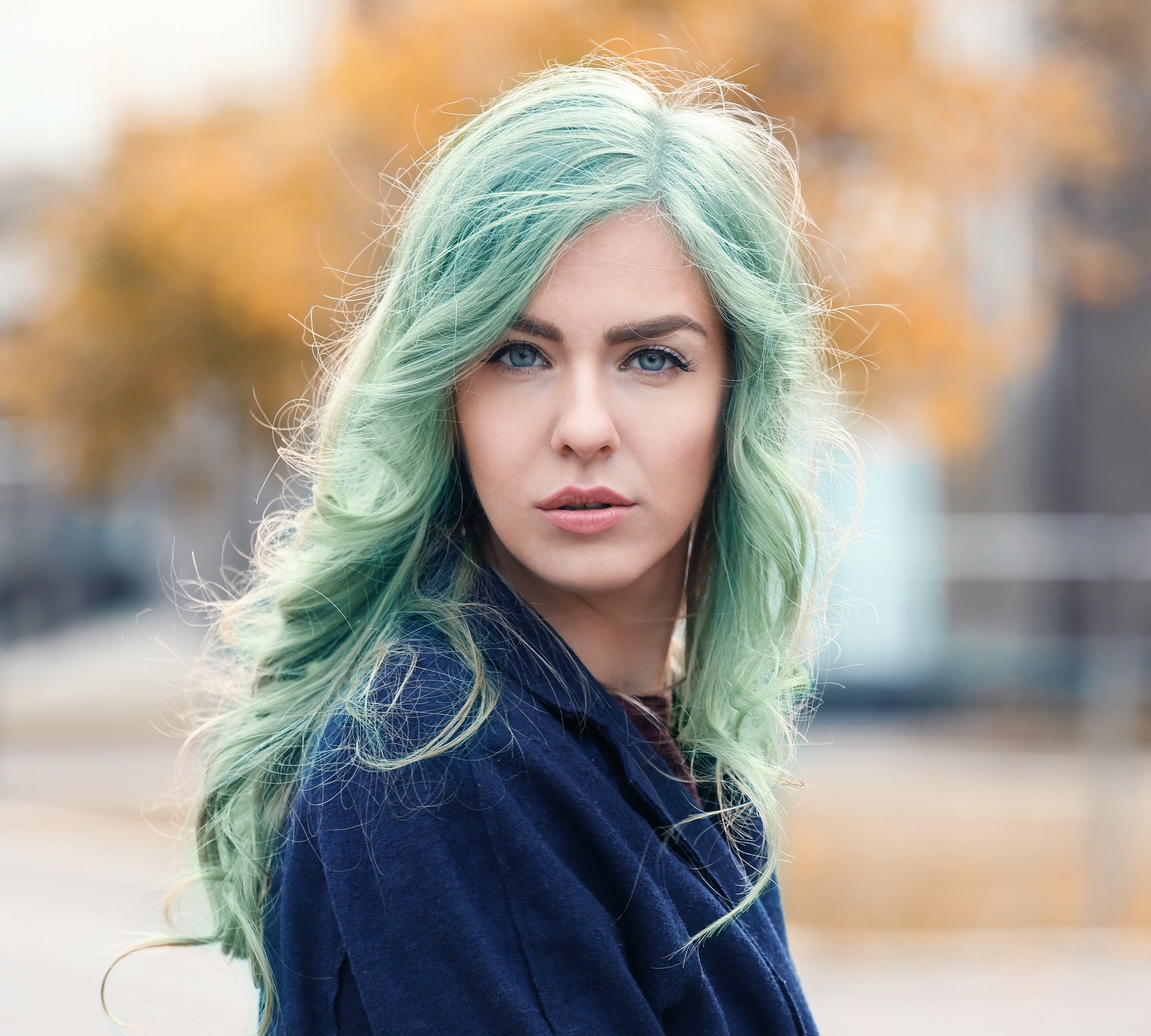 Vibrant hair color: Fair-skinned woman with long mint green hair wearing a blue jacket outdoors