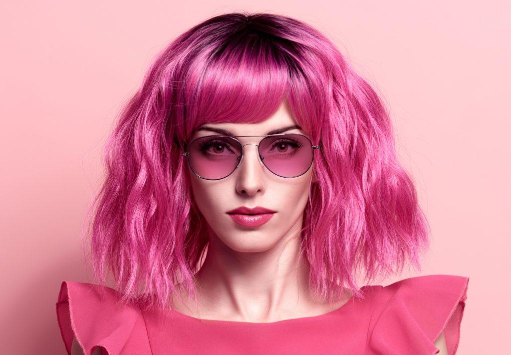 Vibrant hair color: Closeup shot of a woman with a hot pink blunt wavy bob wearing pink shades and a pink shirt