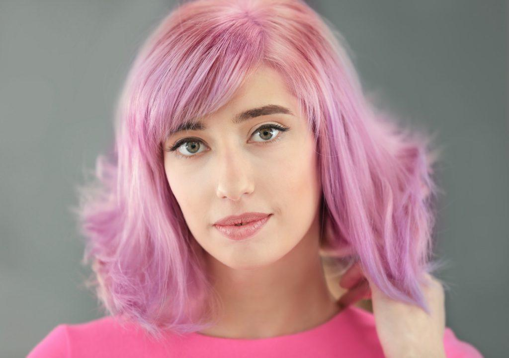 Vibrant hair color: Closeup shot of a woman with lilac long bob with bangs wearing a pink shirt