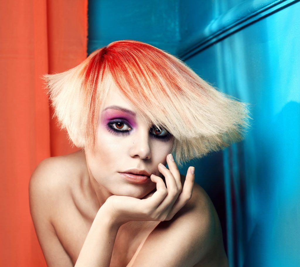 Vibrant hair color: Closeup shot of a woman with orange ombre blunt bob against blue and orange walls