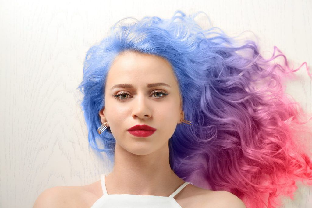 Vibrant hair color: Closeup shot of a woman with blue and pink wavy hair