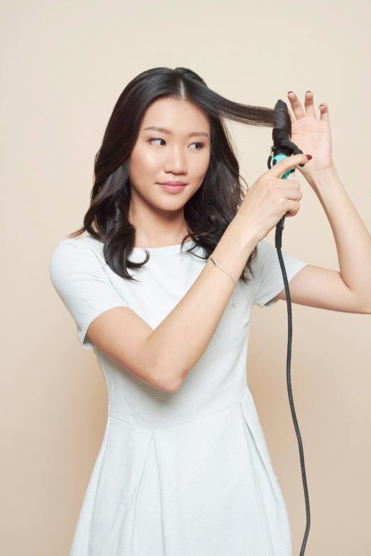 Waterfall braid: Asian woman wearing a white dress curling her black hair with a curling iron