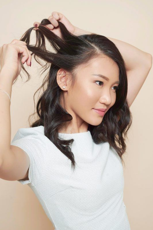 Waterfall braid: Asian woman wearing a white dress styling her long black hair