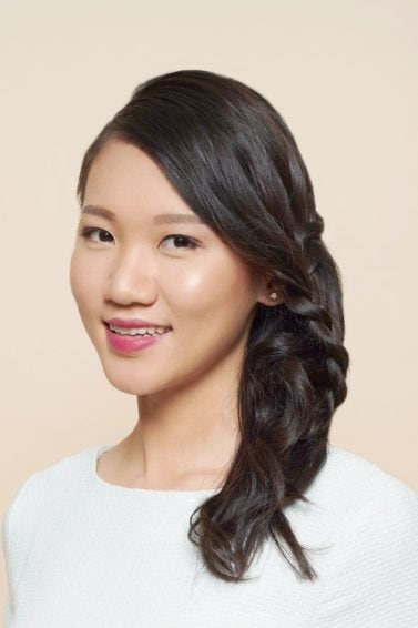 Waterfall braid: Asian woman wearing a white dress with long black hair in a waterfall braid against an oyster-colored background