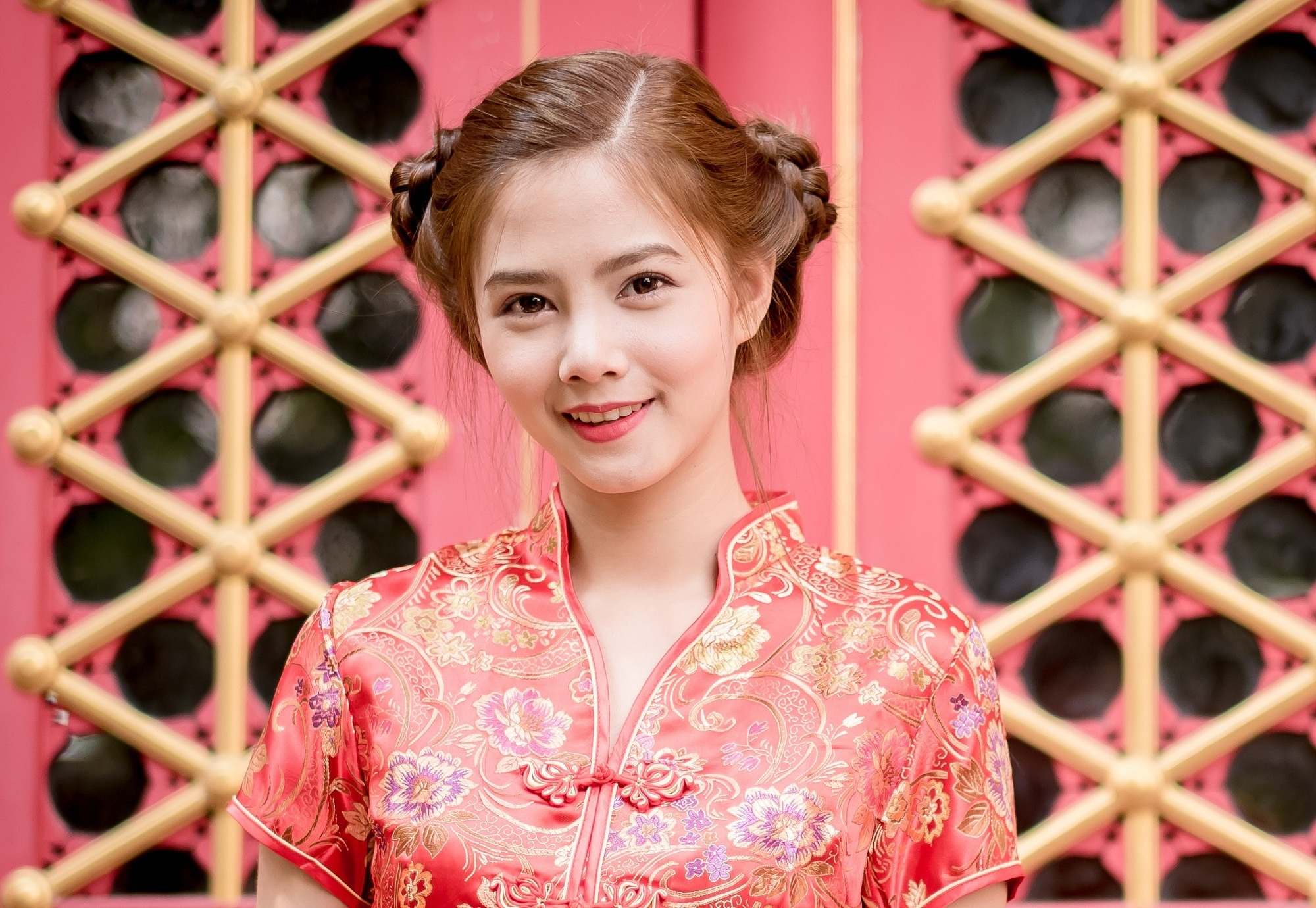 Chinese hairstyles: Asian woman in a red dress with hair in double buns against a Chinese temple door