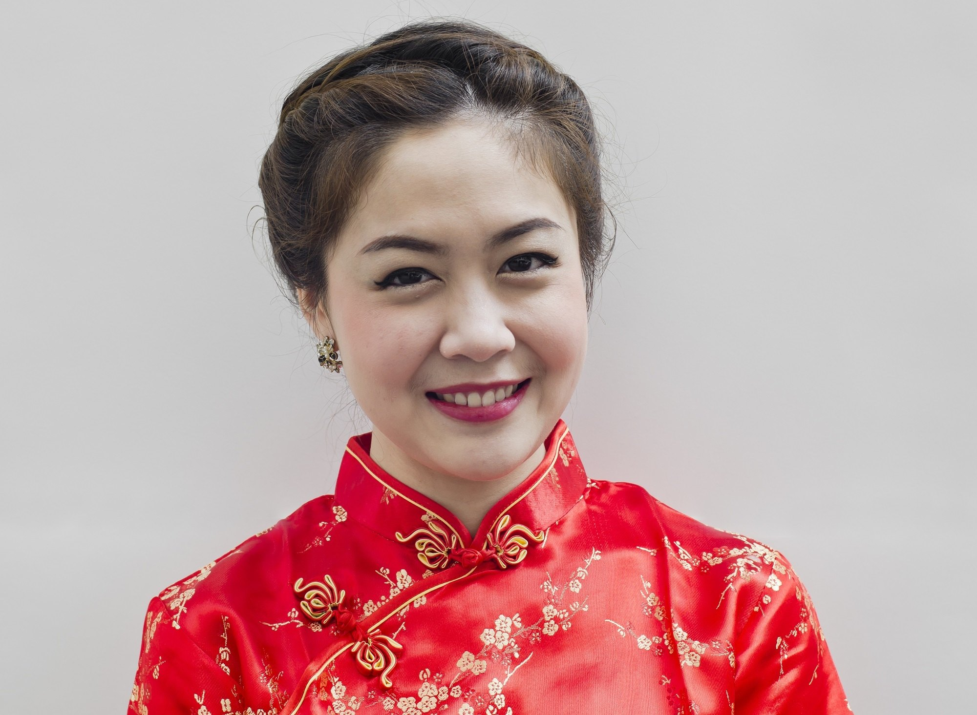 Chinese hairstyles: Closeup shot of an Asian woman wearing a red dress with dark hair in an updo