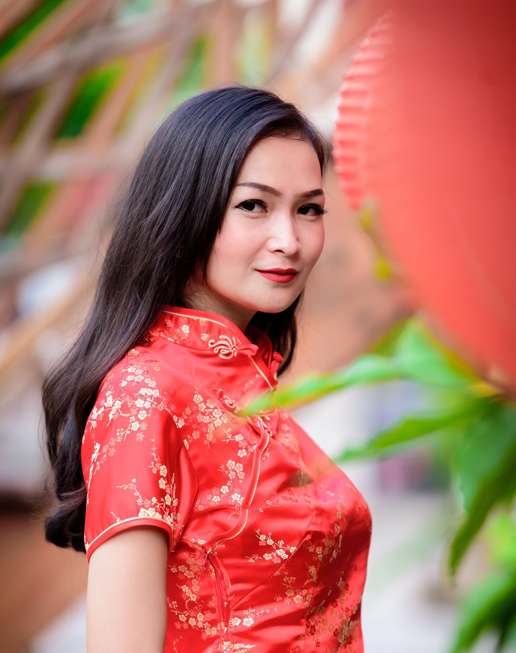 Chinese hairstyles: Closeup shot of a woman with long black hair wearing a red dress in Chinatown