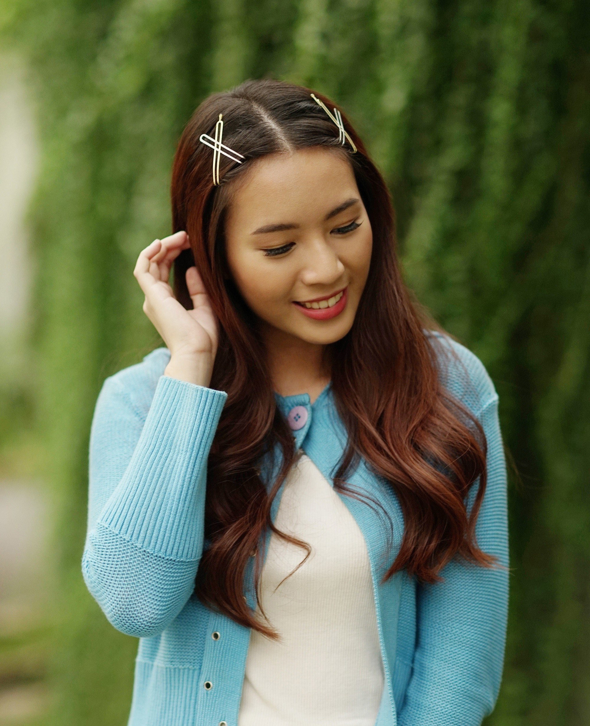Hair clip hairstyles: Asian woman with long dark brown hair with hair clips wearing a blue cardigan outdoors