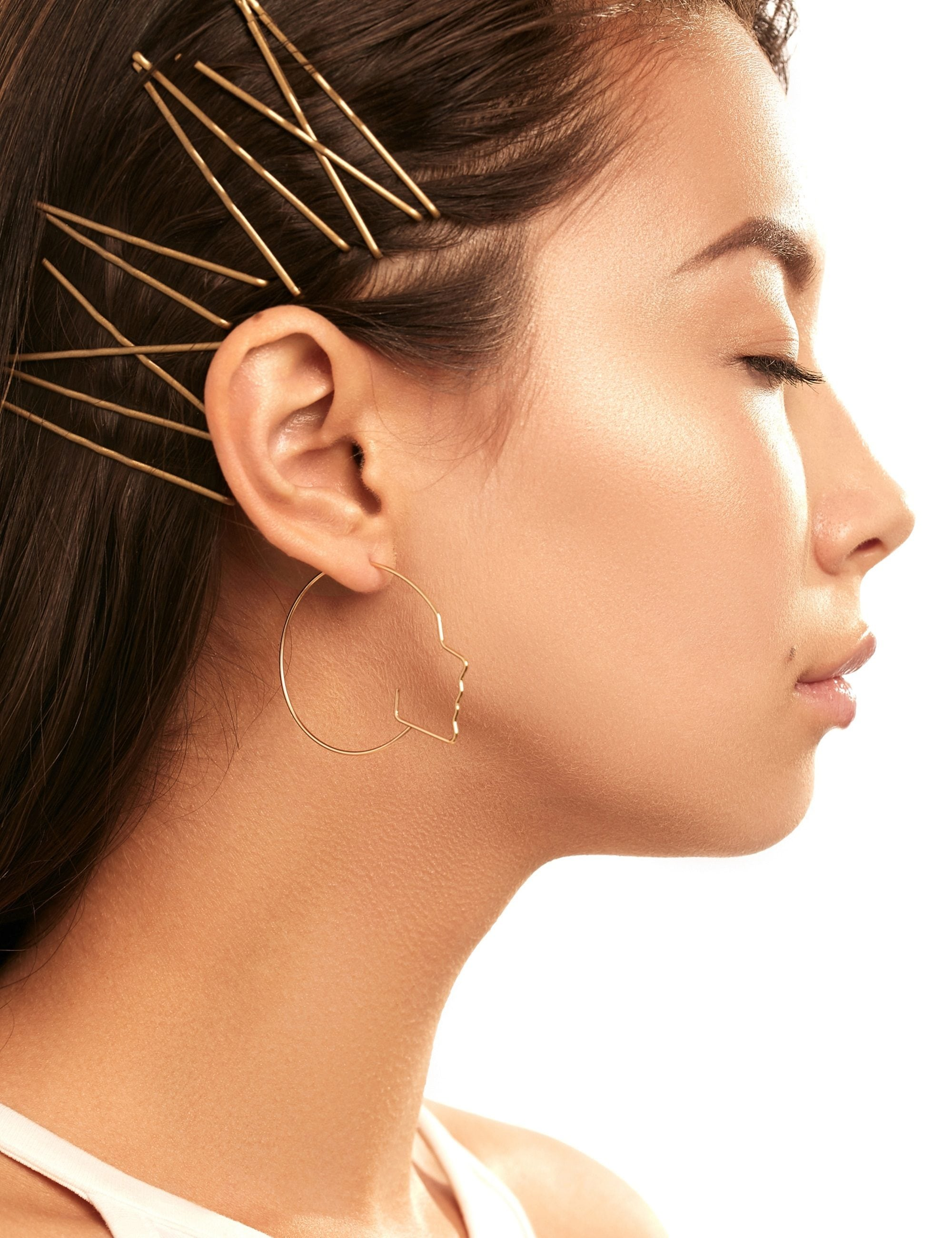 Hair clip hairstyles: Closeup side view of a woman with long black hair with gold bobby pins