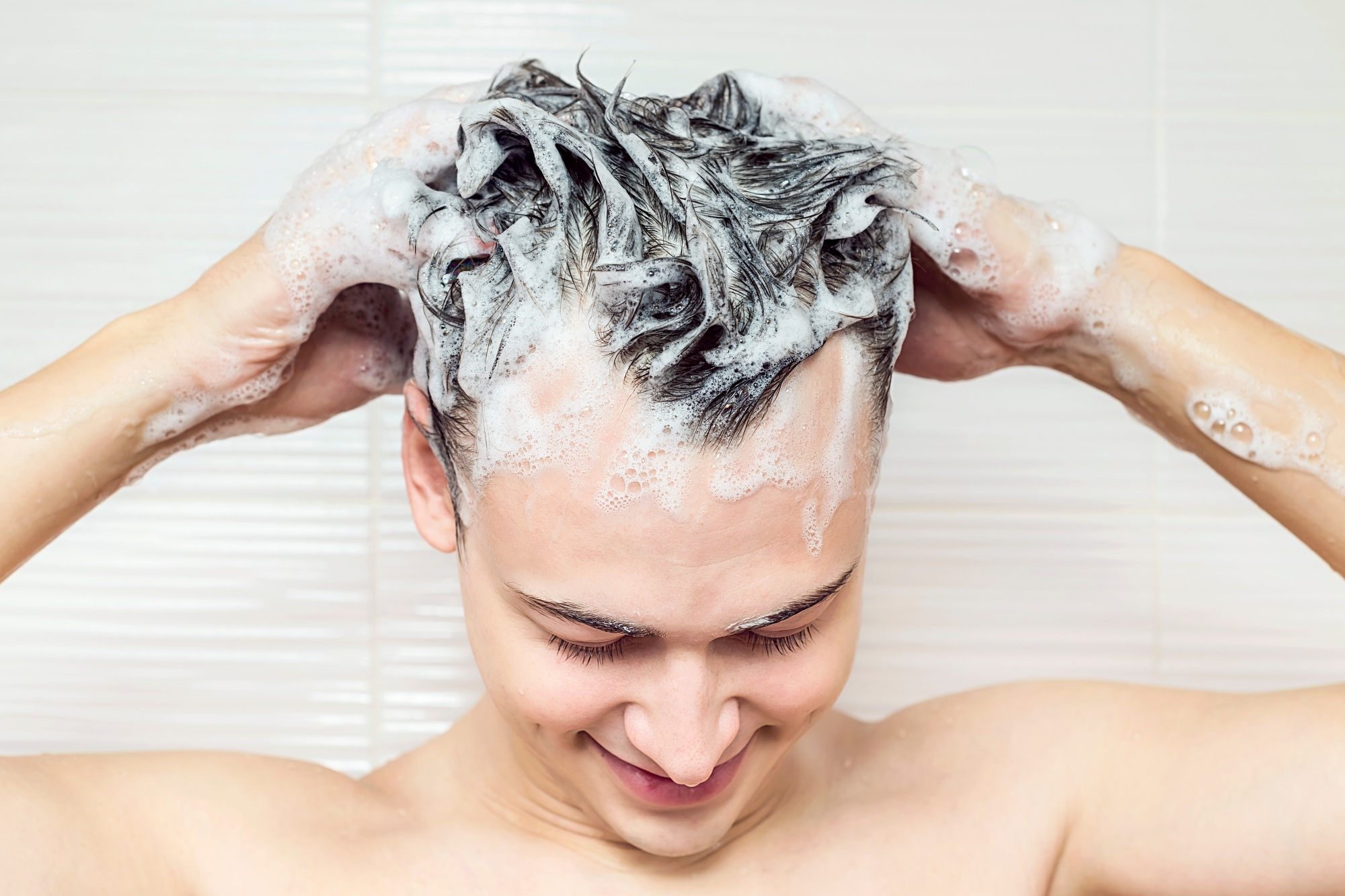 How to deep cleanse your scalp: Closeup shot of a man shampooing his hair