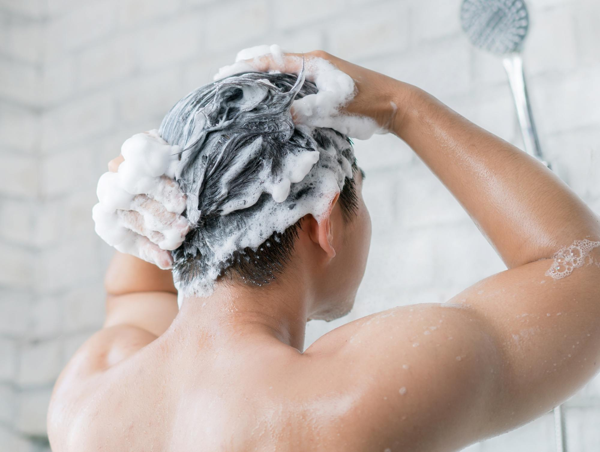 Itchy scalp: Closeup shot of a man shampooing her hair in the shower