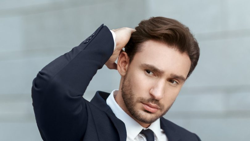 Itchy Scalp: Closeup shot of a man touching her short brown hair wearing a suit outdoors