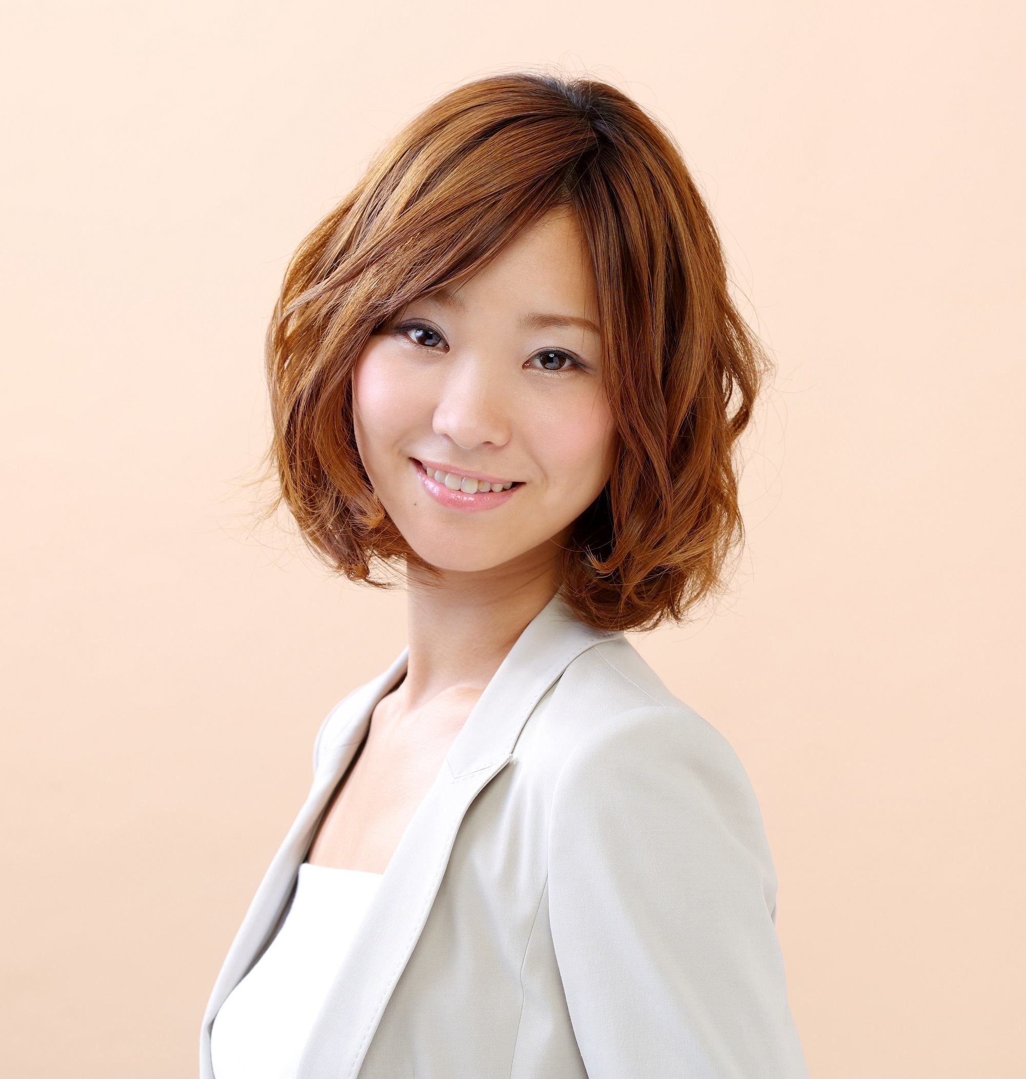 Layered haircuts with bangs: Closeup shot of an Asian woman with short wavy brown hair wearing a gray blazer