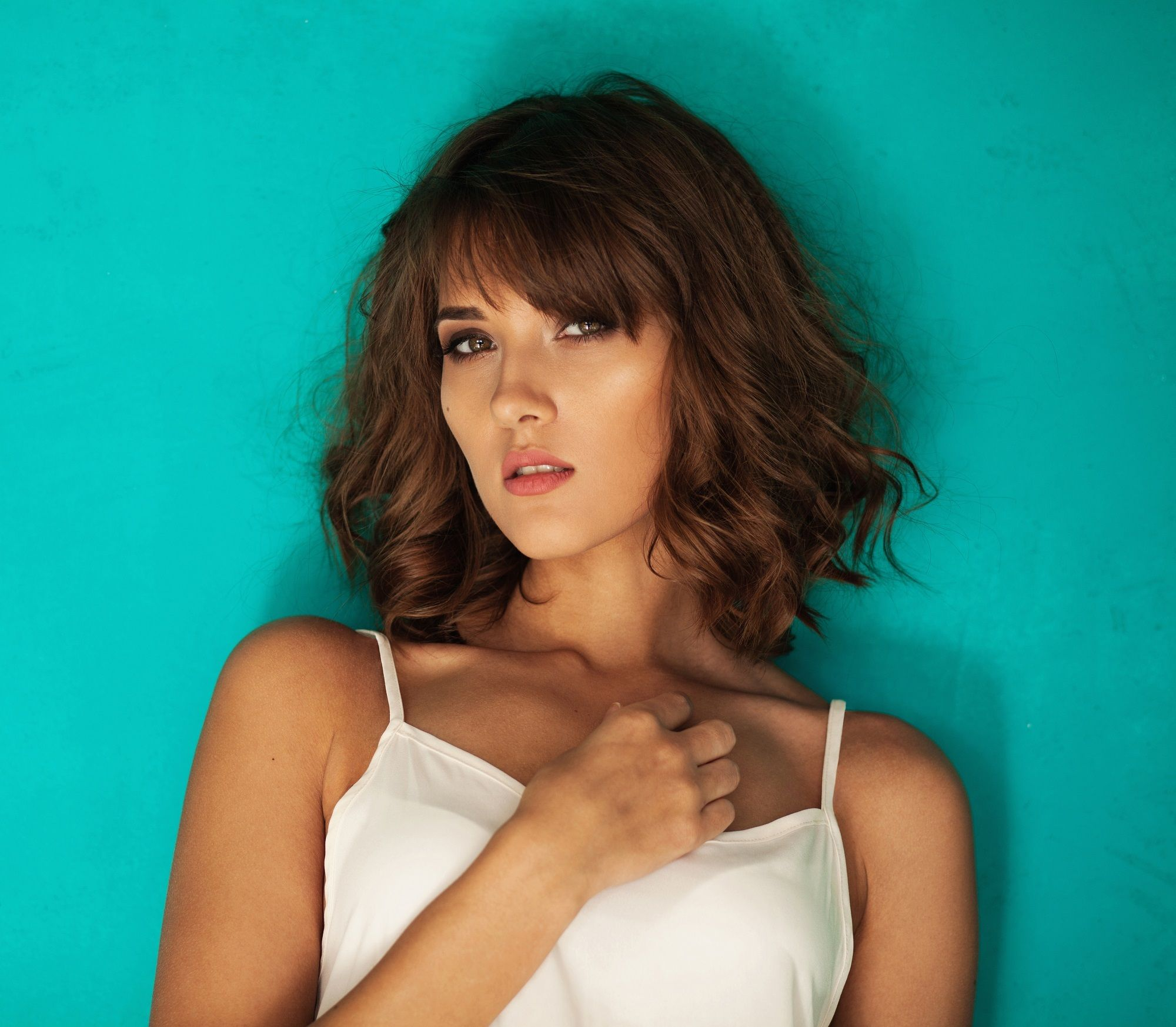 Layered haircuts with bangs: Closeup shot of a woman with wavy brown lob with bangs wearing a white top